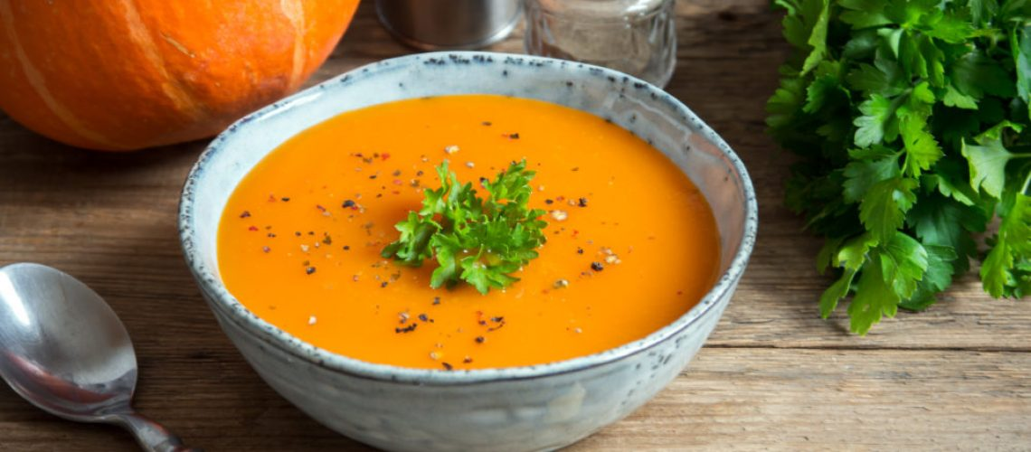 Pumpkin soup and organic pumpkins on rustic wooden table. Seasonal autumn food - Spicy pumpkin ans carrot soup.