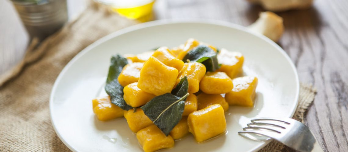 delicious pumpkin gnocchi with sage leaves and olive oil, vegan food