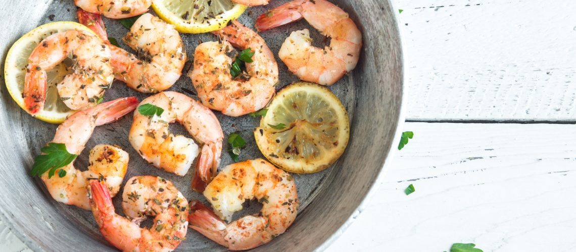 Roasted shrimps with lemon, garlic and herbs. Seafood, shelfish. Shrimps Prawns grilled with spices, garlic and lemon on white background, copy space. Shrimps prawns on pan.